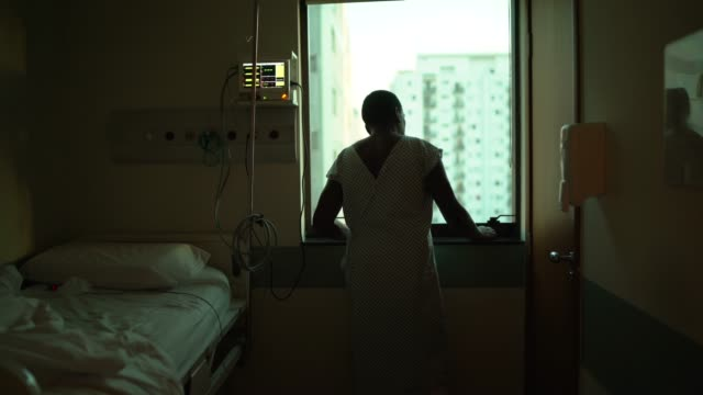 senior patient looking through window at hospital - patient stock videos & royalty-free footage