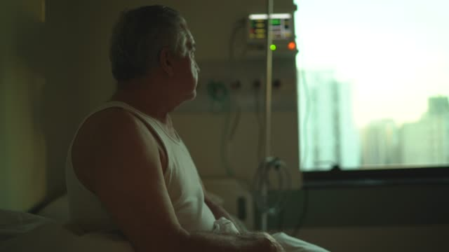 senior patient looking through window at hospital - survival stock videos & royalty-free footage