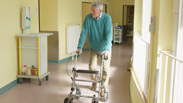 senior patient using mobility walker in corridor - mobility walker stock videos and b-roll footage