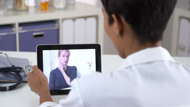 senior patient video chatting with doctor on tablet computer - 人の首点の映像素材/bロール