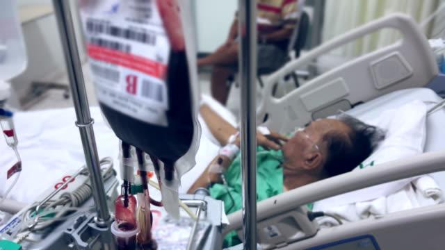ältere patienten wurde blut im krankenhaus gegeben. - nadel pflanzenbestandteile stock-videos und b-roll-filmmaterial