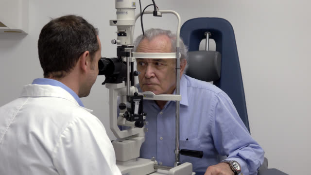 senior patient with his ophthalmologist who is doing an eye exam - ophthalmologist stock videos and b-roll footage