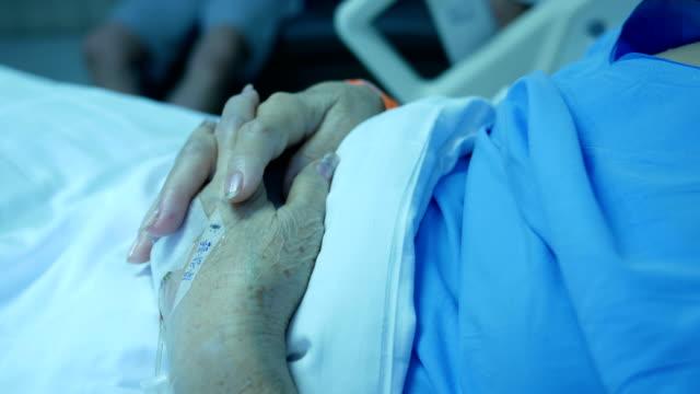 senior patient's hand resting on bed , saline