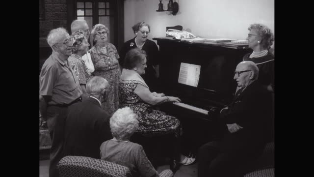 MS Senior people gathered around piano and singing / United States
