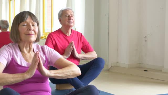 Senior people meditating with yoga teacher