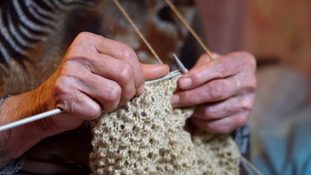 罰金と審美的、近くおばあちゃんの編み物上級者の手しわの新しい冬のセーターを着て、アクティブな退職者の作業の完全な。 - winter点の映像素材/bロール