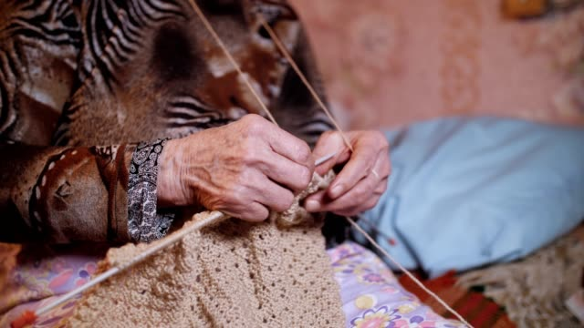 a senior person knitting fine and esthetically, close up of a grandma hands full of wrinkles working on a new winter sweater, active retirees. - ethnicity stock videos & royalty-free footage