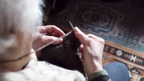 vídeos y material grabado en eventos de stock de pov. una persona mayor que hace punto fino y estético, cerca de las manos de una abuela llenas de arrugas que trabajan en un nuevo suéter del invierno, jubilados activos. - pasatiempos