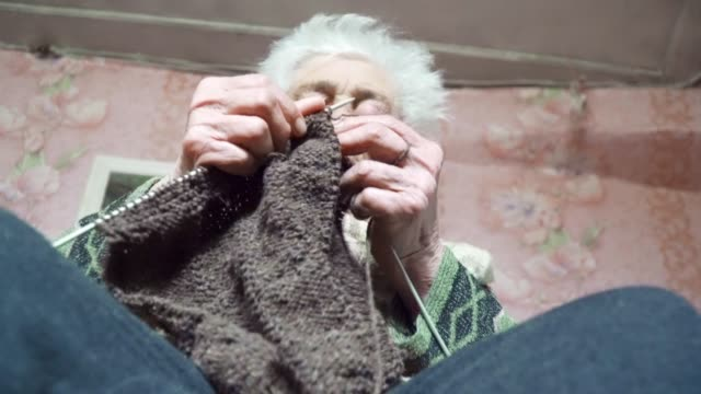 vídeos de stock e filmes b-roll de a senior person knitting fine and esthetically, close up of a grandma's hands full of wrinkles working on a new winter sweater, active retirees. - camisola