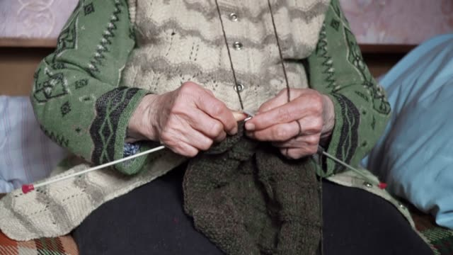 vídeos de stock e filmes b-roll de a senior person knitting fine and esthetically, close up of a grandma's hands full of wrinkles working on a new winter sweater, active retirees. - tricotar