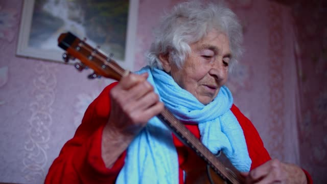 vídeos de stock e filmes b-roll de a senior person learning how to play the guitar from the internet. music and entertainment. portrait of a grandmother with wrinkles, enjoying the music and having fun playing. - comunidade de aposentados