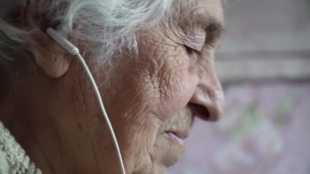 a senior person listening to music with a set of headphones and a phone, entertainment, close-up portrait of a grandmother, wrinkles, enjoying the music, dancing with the rhythm, fun, rose background. - over 80 stock videos & royalty-free footage