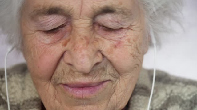 a senior person listening to music with a set of headphones and a phone, entertainment, close-up portrait of a grandmother, wrinkles, enjoying the music, dancing with the rhythm, fun, rose background. - headphones stock videos & royalty-free footage