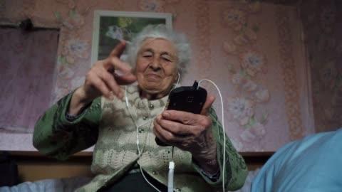 vídeos y material grabado en eventos de stock de una persona mayor escuchando música con un conjunto de auriculares y un teléfono, entretenimiento, disparo mediano retrato de una abuela, arrugas, disfrutando de la música, bailando con el ritmo, diversión, fondo de rosa. - bailar