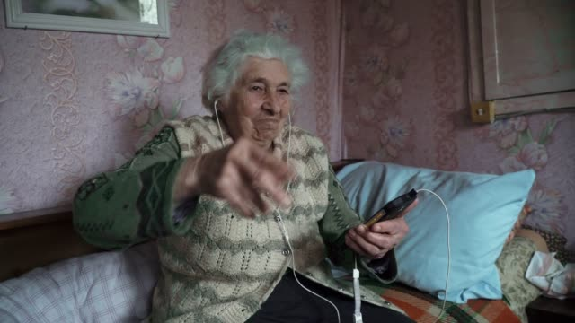 a senior person listening to music with a set of headphones and a phone, entertainment, close-up portrait of a grandmother, wrinkles, enjoying the music, dancing with the rhythm, fun, rose background. - rhythm stock videos and b-roll footage