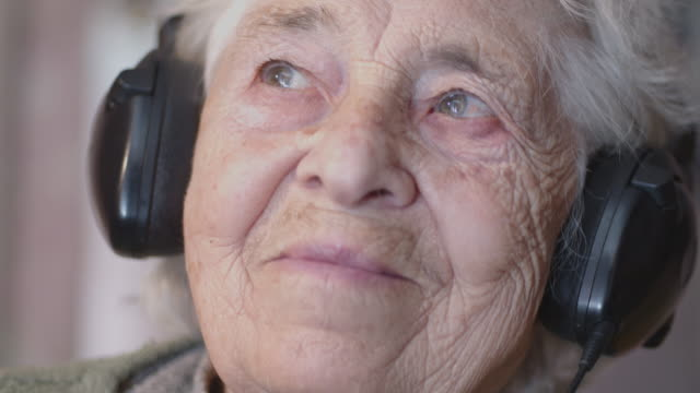 a senior person listening to music with a set of headphones and a phone, entertainment, close-up shot portrait of a grandmother, wrinkles, enjoying the music, dancing with the rhythm, fun. - headphones stock videos & royalty-free footage