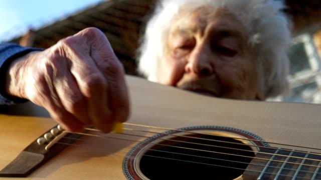 vídeos de stock, filmes e b-roll de uma pessoa sênior que joga a guitarra, música, entretenimento, ao ar livre, retrato médio do tiro de uma avó, enrugamentos, apreciando a música, divertimento, - violão