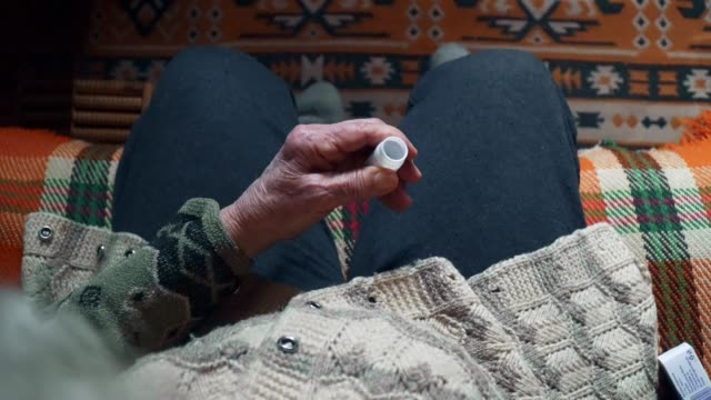 pov. a senior person taking medicine, pills, close up of a grandma's hands full of wrinkles putting the pills in her hand. - taking medicine stock videos & royalty-free footage