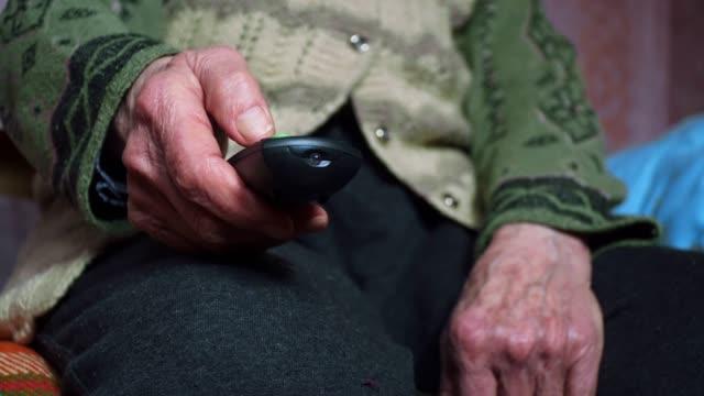 テレビを見ているシニアの人, 娯楽, リモートコントローラを使用してしわの完全なおばあちゃんの手のクローズアップ. - テレビのリモコン点の映像素材/bロール