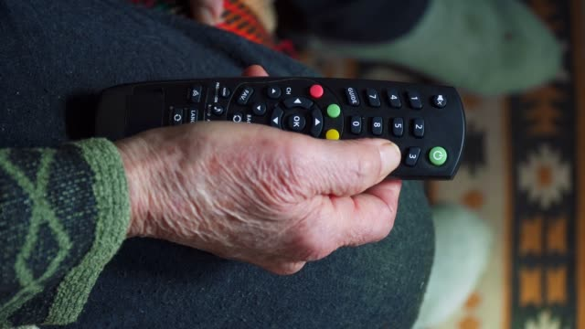 vídeos de stock e filmes b-roll de a senior person watching tv, entertainment, close up of a grandma's hands full of wrinkles using a remote controller. - controlo remoto