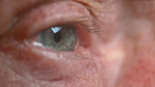 ecu senior person's blue eye opening - man blinking stock videos & royalty-free footage