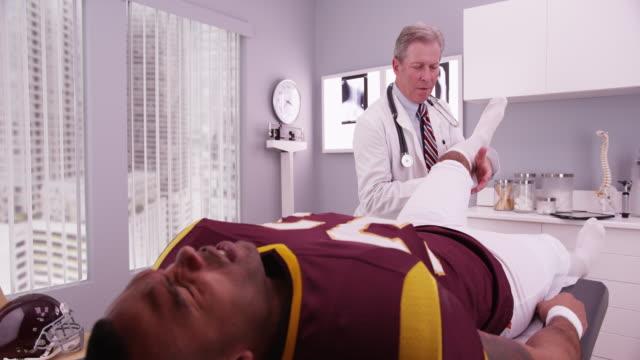 vídeos de stock, filmes e b-roll de senior physical therapist examining sports injury of college athlete - physical injury