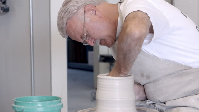 ms ts senior potter sits at pottery wheel shaping wet clay with his bare hand / palm springs, california, usa - potter stock videos & royalty-free footage