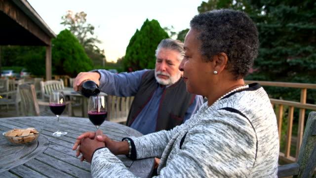 vídeos de stock, filmes e b-roll de senior, derramando os copos de vinho tinto durante a degustação de vinhos na adega - cabelo branco