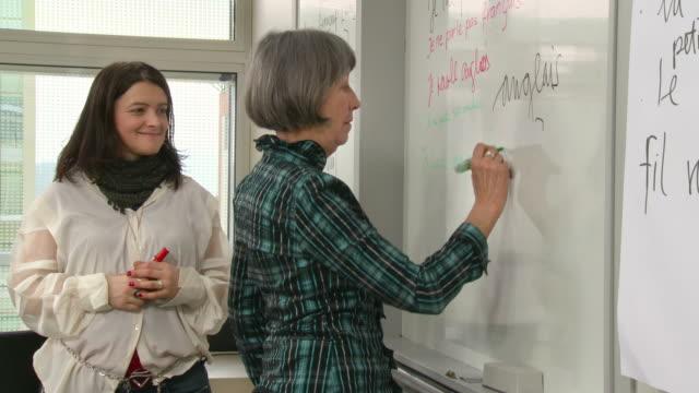 vidéos et rushes de hd: senior s'entraîner écrire en français sur tableau noir - devant
