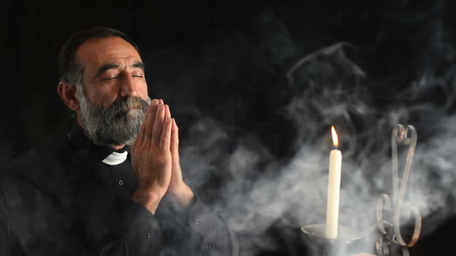 senior priest praying in dark under candle light - priest stock videos & royalty-free footage