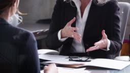 Senior professional woman gesturing at a meeting