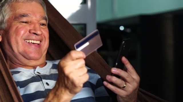vídeos de stock, filmes e b-roll de senior compra alguns itens na internet - brasileiro pardo