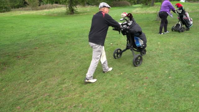 vídeos y material grabado en eventos de stock de a senior pushing their golf carts. - accesorio de cabeza