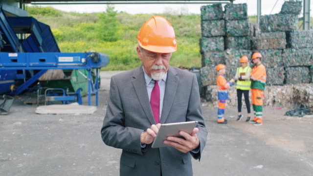 senior recycling specialist outdoors with digital tablet - waste management stock videos & royalty-free footage