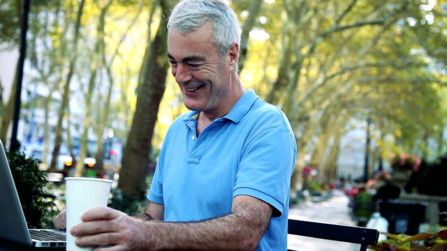 senior relaxing while texting at the park in new york - mature men stock videos & royalty-free footage