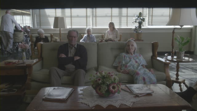 stockvideo's en b-roll-footage met senior residents sitting in the common room of a retirement home. - woongemeenschap ouderen