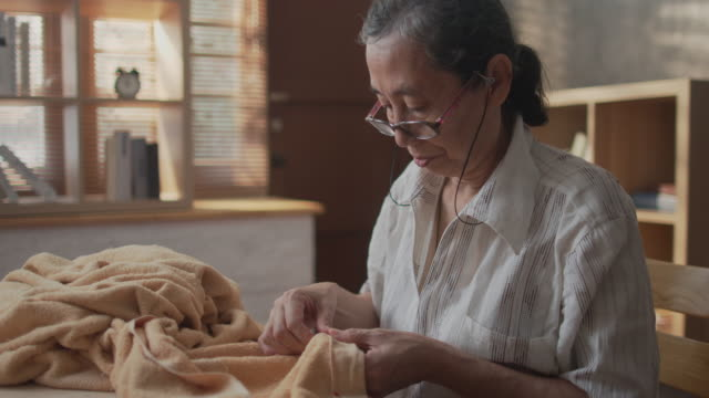 senior retirement asian female enjoy sewing and knitting at apartment - determination stock videos & royalty-free footage