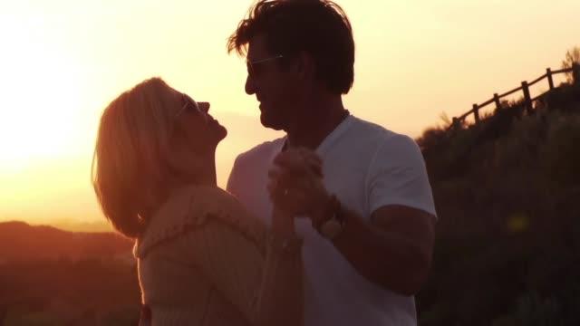 vídeos de stock e filmes b-roll de senior road trip couple lover sunset dancing kissing romance - carro descapotável