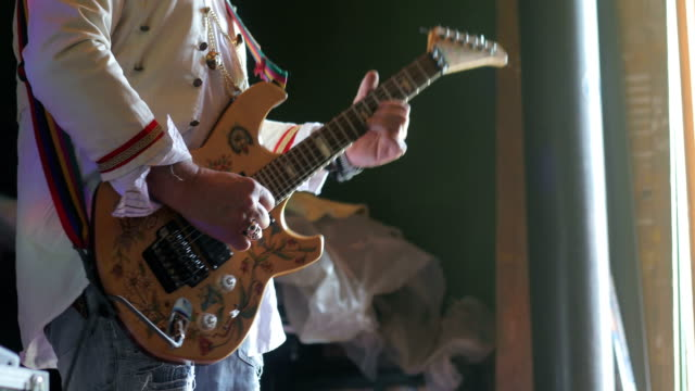 senior rock musician playing electric guitar indoors - customized stock videos and b-roll footage