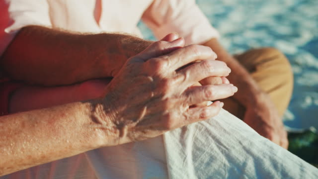 senior romantic couple holding hands at beach - holding hands stock videos & royalty-free footage