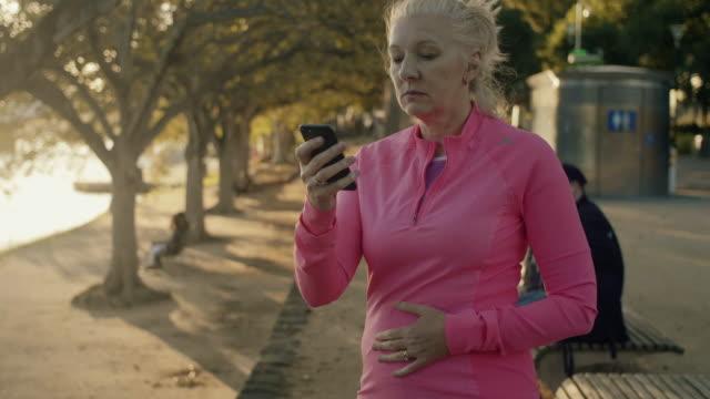 Senior runner checking smart phone