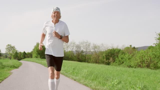 SLO MO TS Senior corridore jogging sulla strada asfaltata