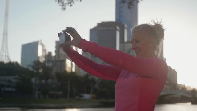 senior runner taking selfie (slow motion) - leisure activity stock videos & royalty-free footage