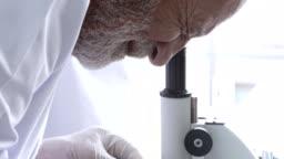 Senior scientist using microscope in laboratory