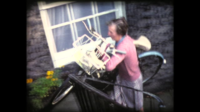 1980 senior scottish woman lifts bicycle and rides off down street - home movie stock videos & royalty-free footage