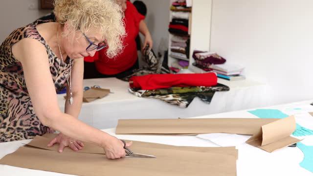 sarta senior che usa le forbici per tagliare con precisione un modello per il design futuro dei vestiti - aggiustare video stock e b–roll