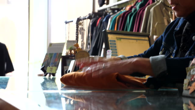 ms senior shop owner wrapping purchase for client at counter in clothing boutique - alternative energy stock videos & royalty-free footage