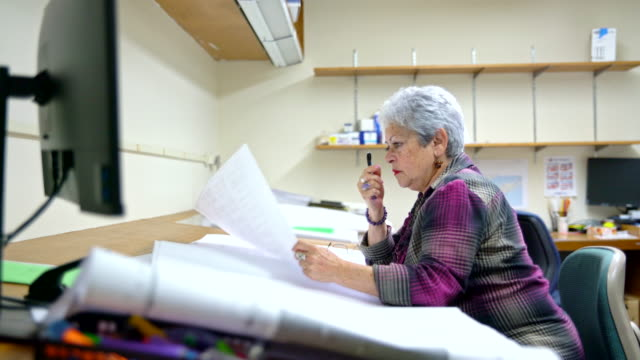 senior silver-haired woman, engineer, measuring the space on the drawing of architectural project with curvimeter. - engineer stock videos & royalty-free footage