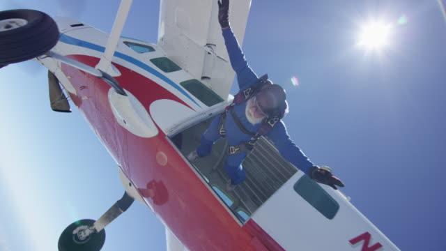 senior skydiver exits airplane - fallschirm stock-videos und b-roll-filmmaterial