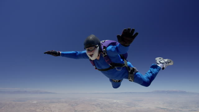 senior skydiver falls through crystal clear sky - senior men stock videos & royalty-free footage